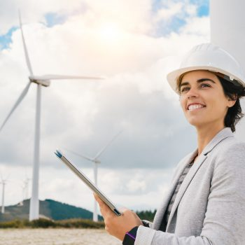 Female engineer smiling past camera with wind turbines in background
