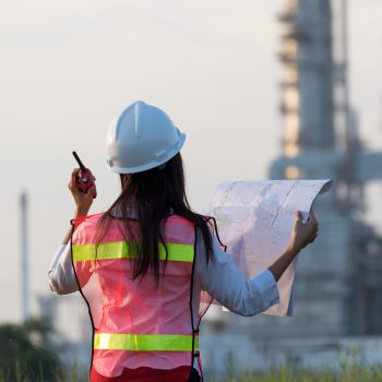 Back view of female engineer in high-vis vest facing an energy plant